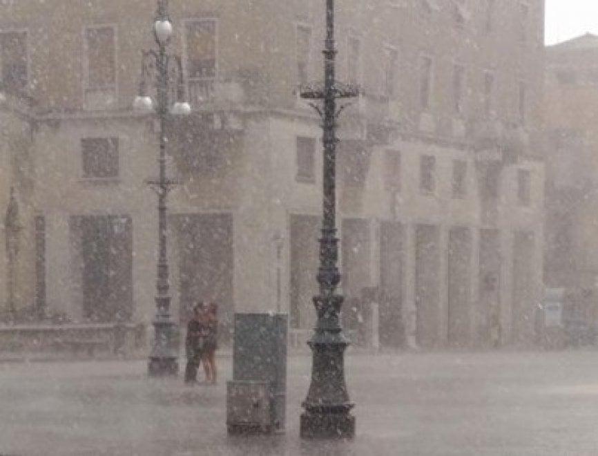 Il bacio virale sotto il nubifragio nel cuore di Lecce