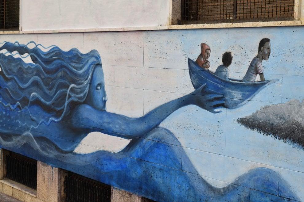 Una sirena salva i bambini migranti nel murale d'artista sulla scuola di Bari