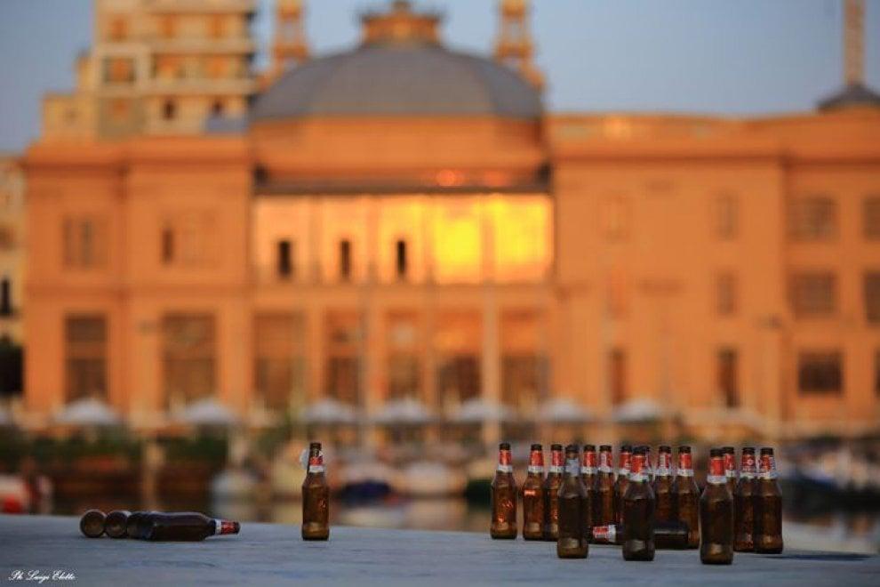 Bari, il risveglio dopo la movida: le bottiglie di birra in fila sul lungomare