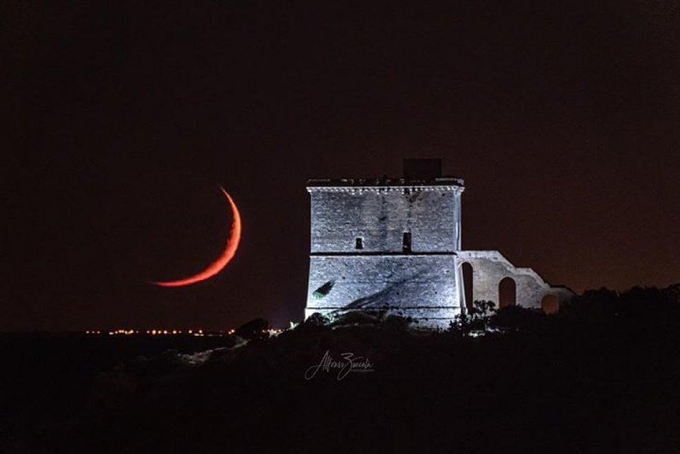 Salento, la falce di luna rossa illumina la Torre dell'Alto: sullo sfondo le luci di Taranto