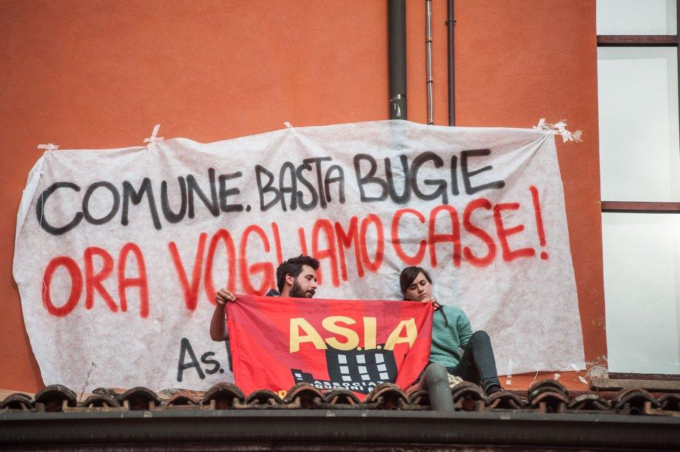 """""""Basta sgomberi"""": Bologna, due attivisti salgono sul tetto del Comune"""