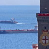 Genova, il benvenuto della Lanterna ai migranti, lo striscione dei portuali