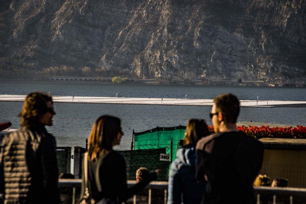 Gli Umarell dei cantieri di Christo: curiosi sulle sponde del lago di Iseo, aspettando di camminare sull'acqua