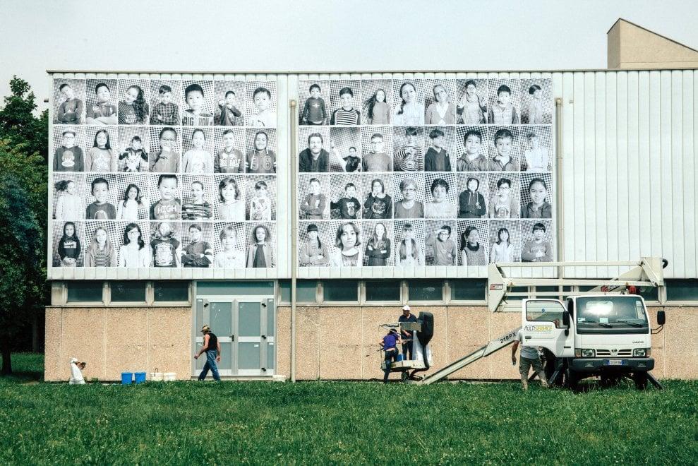 Milano, la scuola tappezzata con le foto degli alunni formato manifesto: l'integrazione si fa anche sui muri