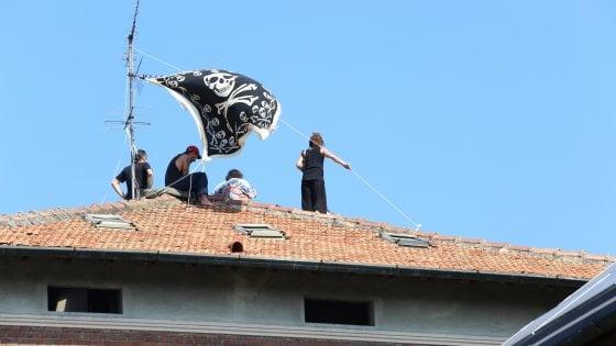 Milano, sgomberato il palazzo della Madonnina oltraggiata: in sette sul tetto per ore con la bandiera dei pirati