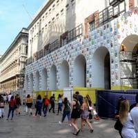 Milano, spuntano maschere colorate sulla facciata della Rinascente: è per la Fashion Week