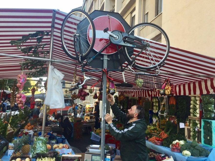 Milano, dimentica la bici in area mercato: gli ambulanti gliel'appendono al palo