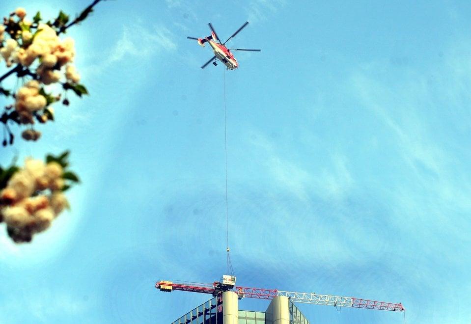 Gli operai acrobati di CityLife, con elicottero e gru al lavoro in cima allo Storto