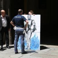 Porti chiusi, provocazione d'artista a Milano: espone quadro con Salvini-Robocop la Digos la blocca