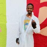 Simboli di pace e bandiere: i richiedenti asilo dipingono il muro del centro di via Corelli