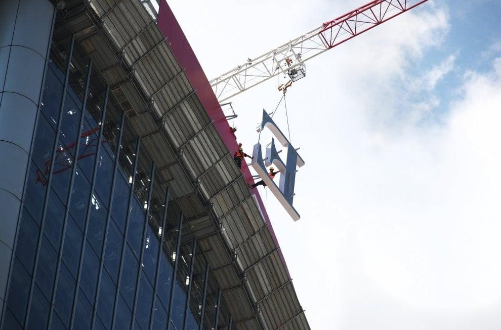 """Milano: """"riggers"""" al lavoro per installare la maxi-insegna sul tetto del grattacielo"""