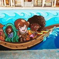 Il viaggio del giovane migrante in un murale nel Milanese: lo street artist dipinge con gli studenti