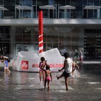 Caldo e afa a Milano: la fontana di piazza Gae Aulenti si trasforma in una piscina