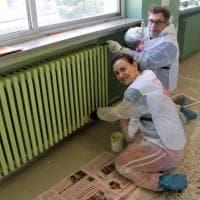 Milano, vernice antismog sui muri della scuola: volontari, studenti e genitori al lavoro coi pennelli