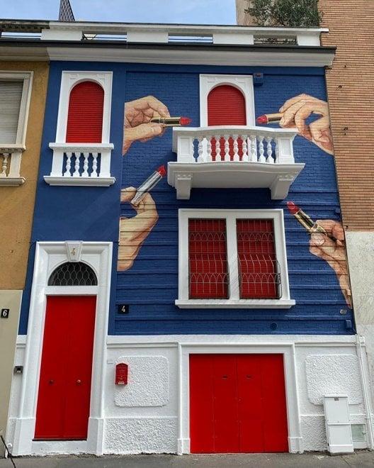 Mani e rossetti sulla facciata del palazzo bianco, rosso e blu: l'insolita tinteggiatura a Milano