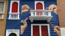 Mani e rossetti sulla facciata del palazzo bianco, rosso e blu