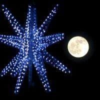 La luna piena fa capolino dalla stella dell'albero di Natale