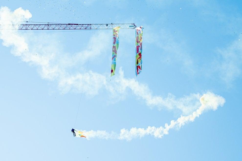 Milano, un uomo sale sulla gru e sventola la bandiera della pace