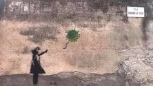 La bambina con il palloncino di Banksy reinterpretata: a volare via è il virus