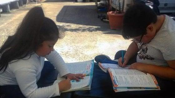 Milano, i fratellini rom fanno i compiti fuori dalla roulotte: niente lezioni online, ma penna e quaderno
