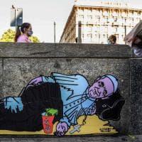 Papa Francesco come un clochard e la Madonna che chiede la carità: la street art sui muri di Milano