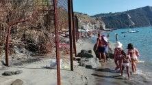 Bagnanti a mare tra i pali di ferro arrugginiti