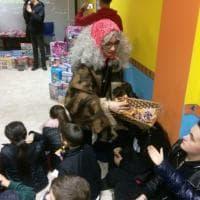 La befana distribuisce giocattoli raccolti nelle discoteche ai bambini della fondazione A' Voce d'è Creature
