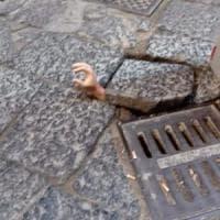 Strade colabrodo a Napoli, la provocazione della mano che esce dalla buca a San Gregorio Armeno