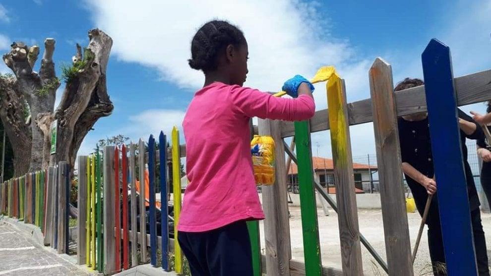Tutti i colori dell'accoglienza: Hermela dipinge la staccionata del parco giochi comunale