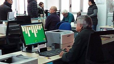 L'impiegato all'Anagrafe gioca al solitario mentre la gente è in fila  foto