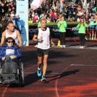 Maratona di Palermo, atleta gareggia spingendo la carrozzina di una ragazza