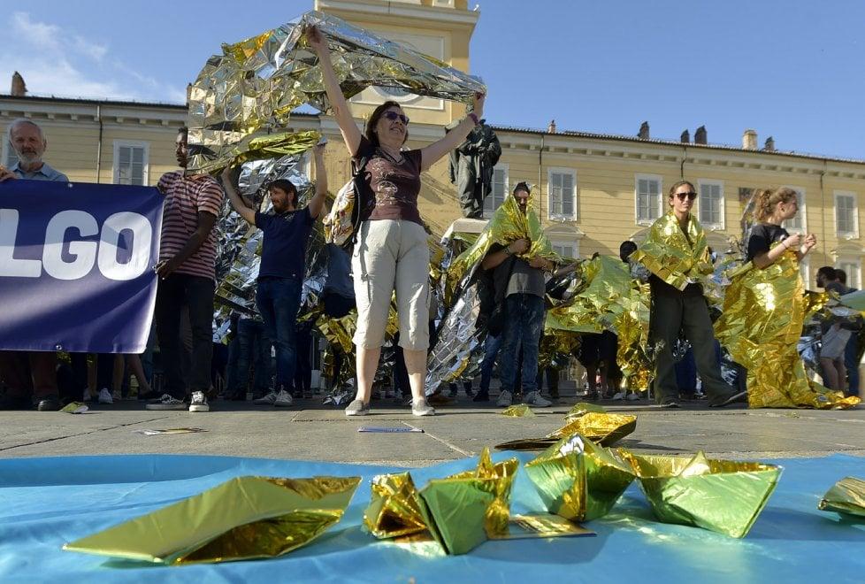 """""""Io accolgo"""": cittadini in piazza a Parma con le coperte termiche - Foto"""