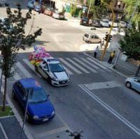 Roma, sulla macchina dei vigili urbani c'è una nuvola di palloncini
