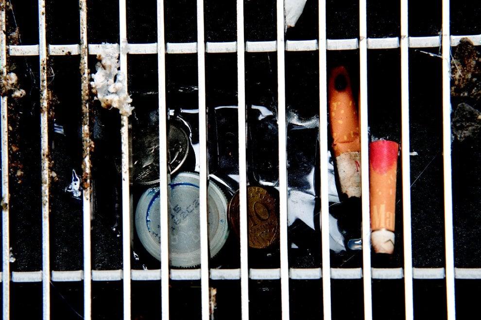 Cicche di sigaretta, plastica e monete: l'arte dai rifiuti impigliati nelle grate