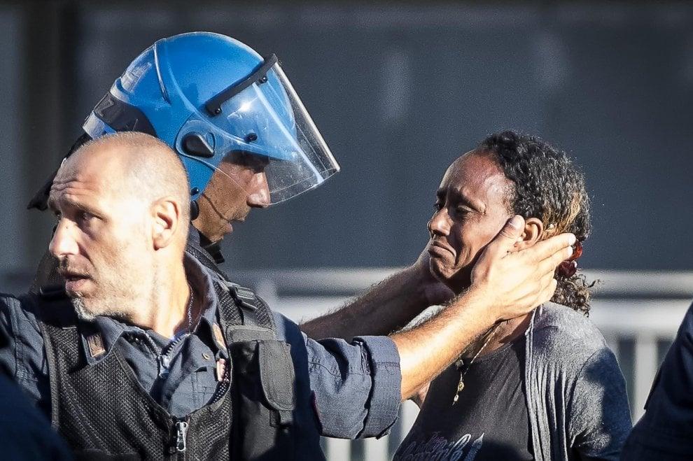 Sgombero migranti, la carezza del poliziotto durante gli scontri