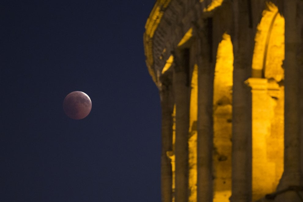 La luna rossa spunta dietro il Colosseo: lo spettacolo dell'eclissi nel cielo di Roma