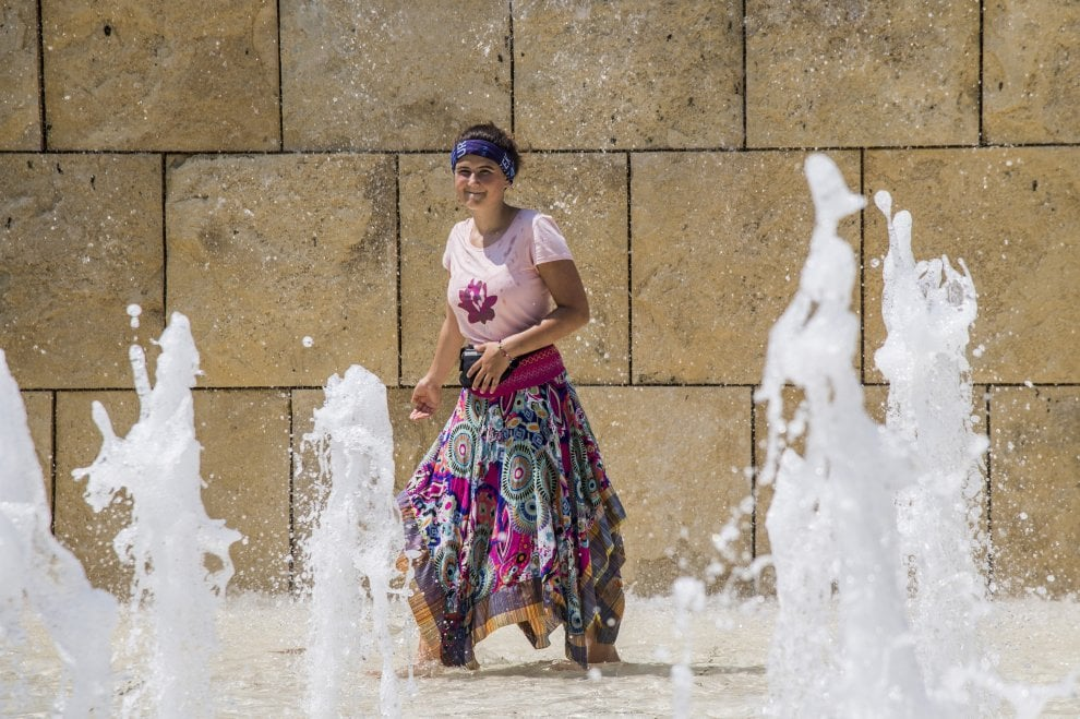 Il grande caldo opprime Roma: turisti  nella fontana dell'Ara Pacis