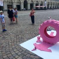 """Torino, un copertone e una vita spezzata: la misteriosa performance dell'""""uomo in rosa"""" in piazza San Carlo"""