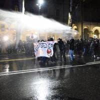 Sassaiola dal corteo antifascista a Torino, la polizia ferma i manifestanti con idranti e...