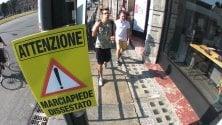 """In centro un cartello avverte:""""Attenzione marciapiede dissestato"""""""
