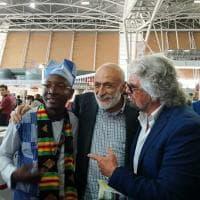 """Beppe Grillo a sorpresa al Salone del Gusto di Torino, foto con i delegati ivoriani: """"Questa la mandiamo a Salvini"""". E alle 13 arriva Appendino"""