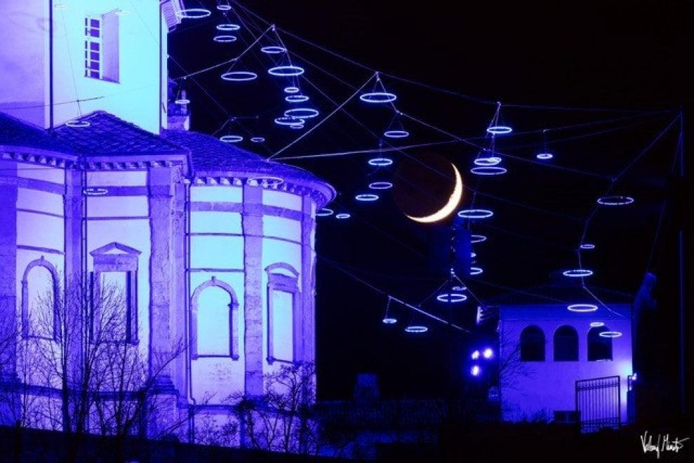 Lo spettacolo della luna su Torino nella notte colorata dalle luci blu
