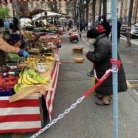 """Torino, nel mercato transennato la spesa si fa con la """"prolunga anticontagio"""""""