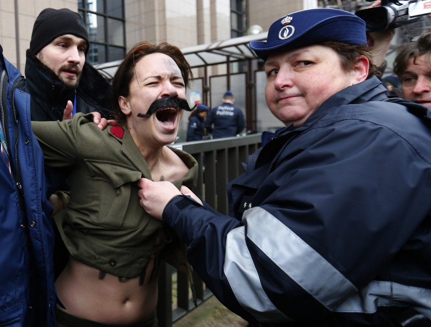 un agente (brutto) copre una Femen