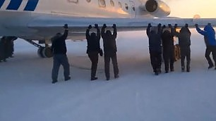 L'aereo è bloccato dal ghiaccio Passeggeri spingono a mano