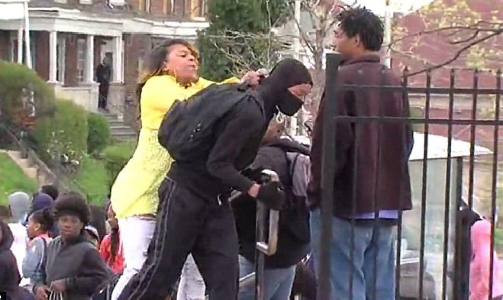Baltimora, la donna che trascina via il figlio dagli scontri