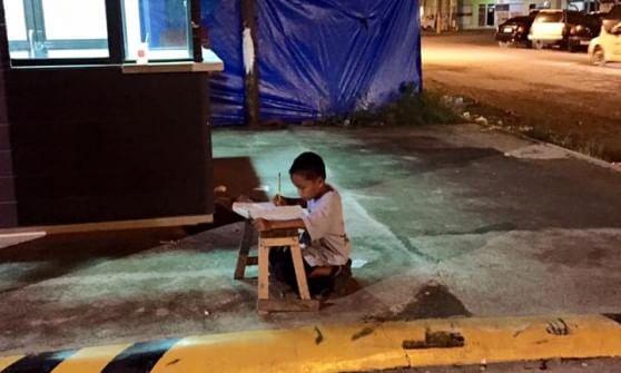 Il bambino studia alla luce del lampione foto simbolo della lotta