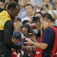 Il cameraman si scusa con Bolt. E sul podio gli regala un braccialetto