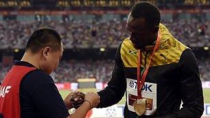 Il cameraman si scusa con Bolt sul podio gli regala un braccialetto    Video  Il campione travolto