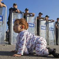 Migranti, bimba gattona a ridosso dei poliziotti con scudi in Turchia